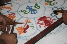 Buddhistische Mönche malen ein Mandala mit farbigem Puder